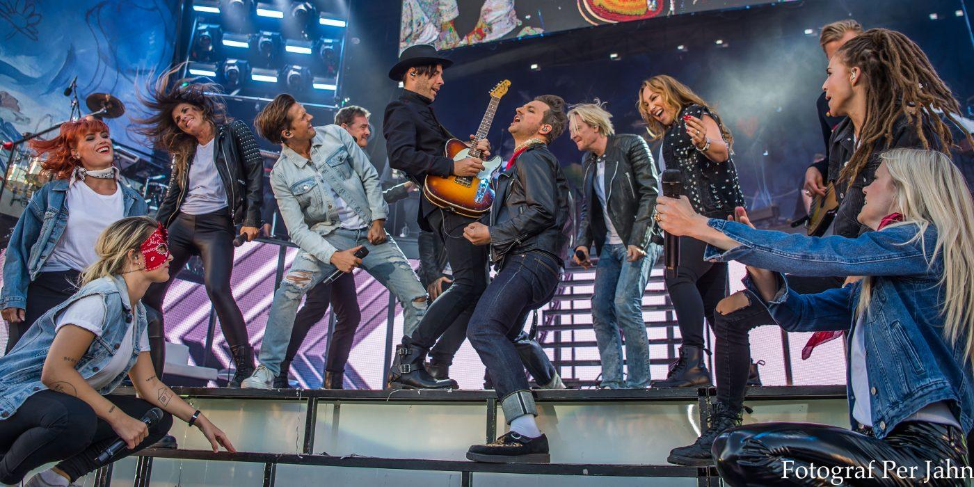 Artister sjunger tillsammans på scenen.