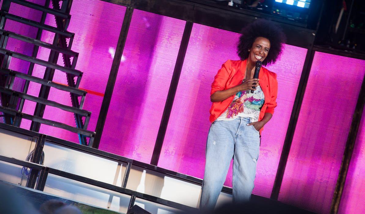 Marika Carlsson på scen framför lila bakgrund.